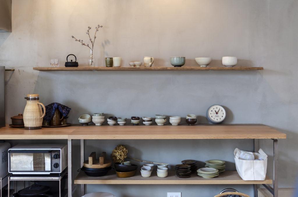 キッチンの延長上にあるカウンターとその上の棚に置かれているのは陶芸作家の作品で売り物。ここに置いてあると購入する人がけっこういるという。その下にあるのは「料理のイベントの時に使ってください」と作家の人からいただいたもの。