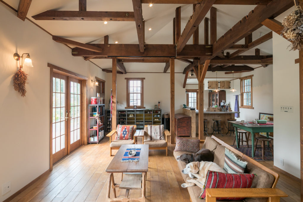 天井を抜いて古い梁を見せた。切妻屋根を生かした三角の天井は白に。「ソファは実家にあった母の嫁入り道具を引き継いで大事に使っています」