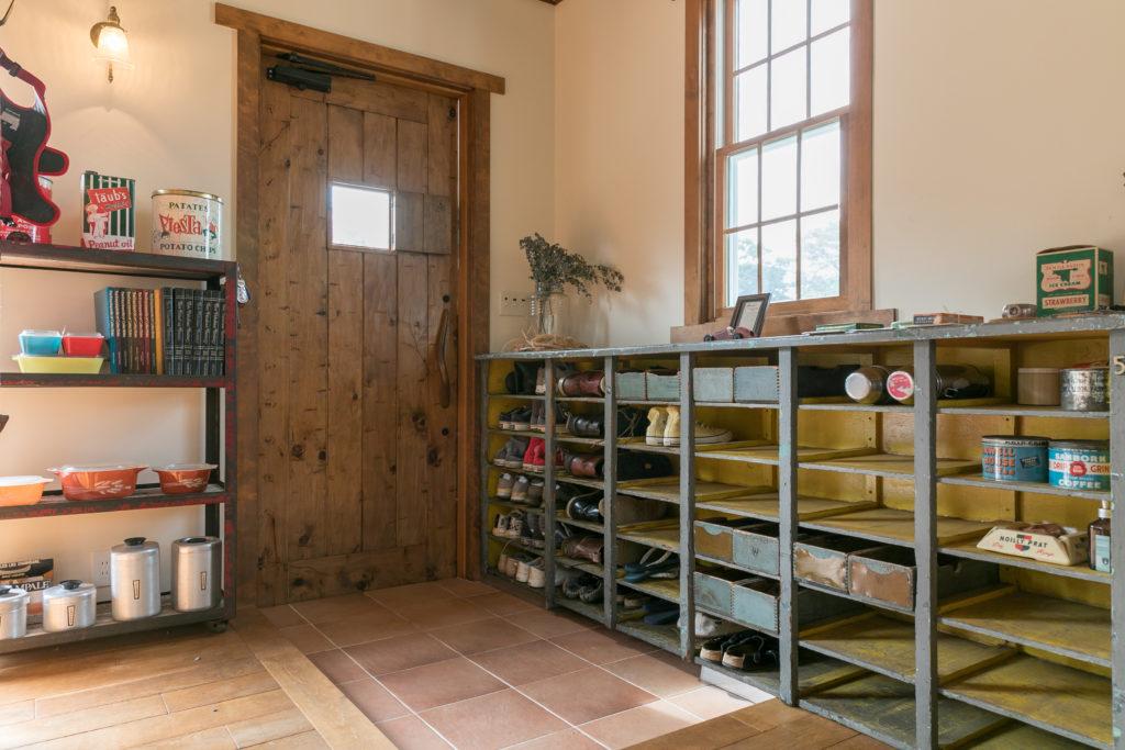 玄関扉は『GALLUP』でオーダーしたハンドメイドのヴィンテージ。下駄箱にしたヴィンテージの棚も『GALUP』で。「窓の高さとピッタリのサイズだったので、購入を即決しました」