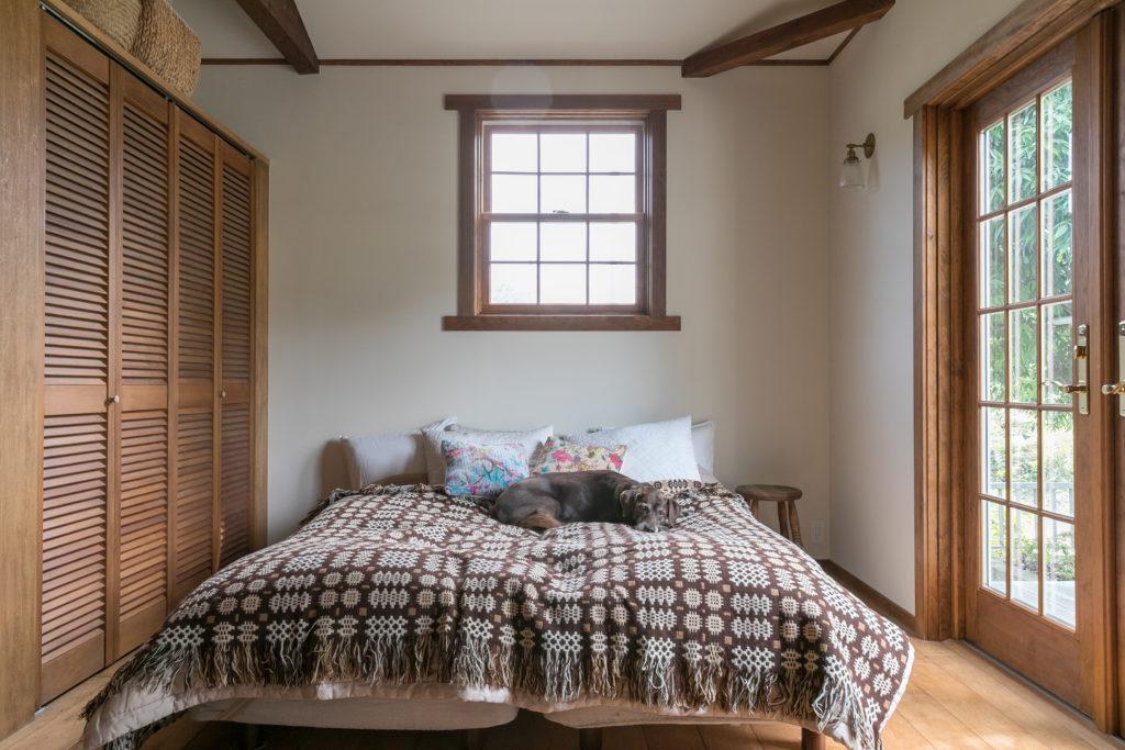 2面採光の明るいベッドルーム。ベッドルームからも、木製の観音開きのドアから外のデッキに出ることができる。