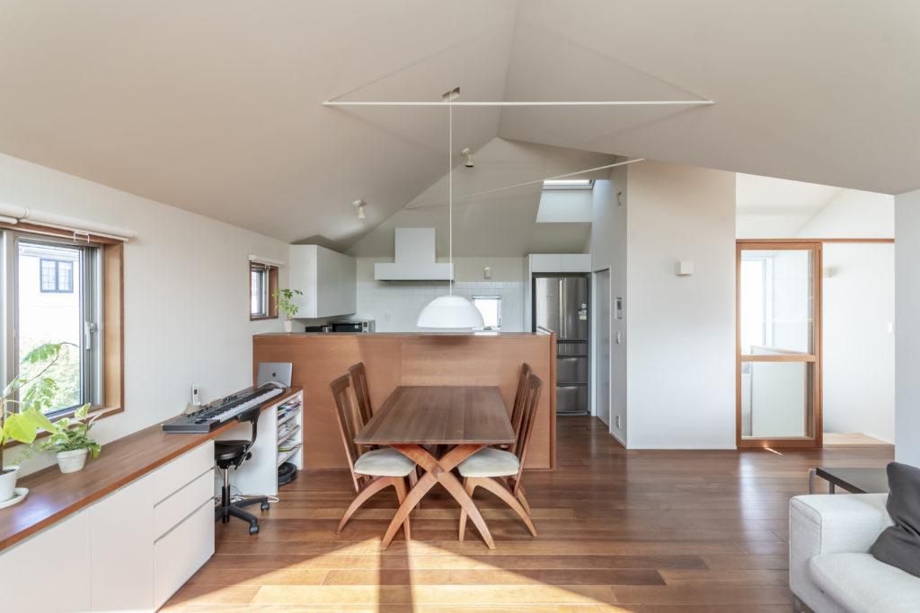 リビングからダイニングとキッチンを見る。キッチンは夫婦2人で作業ができるよう広めにつくった。家型の天井を交差させた部分は少し不思議な印象を与える造形になっている。