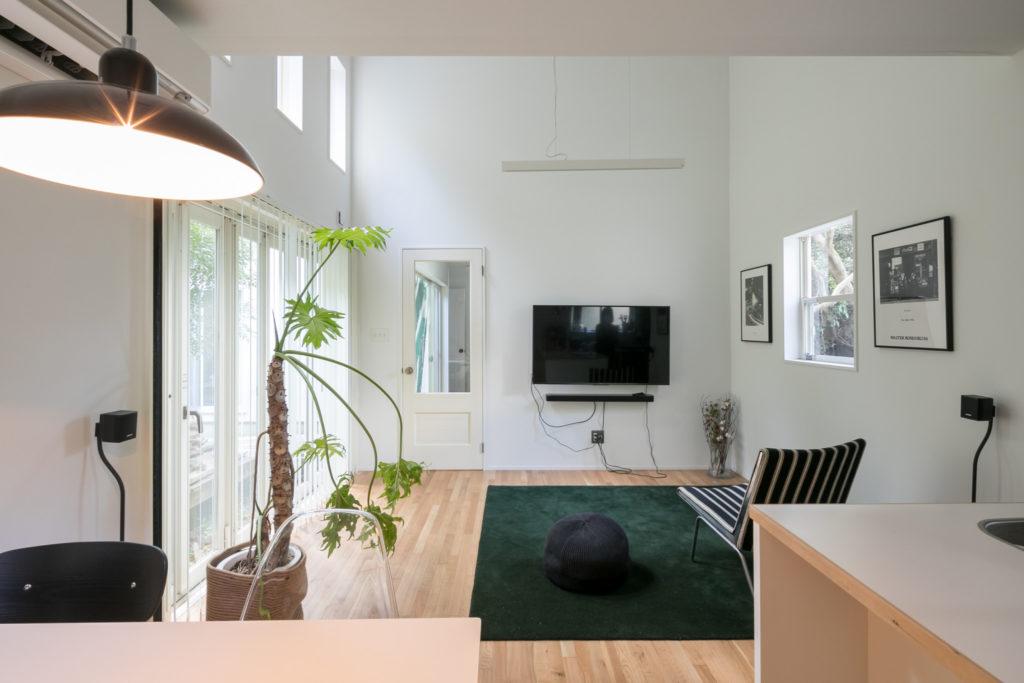 大きな窓から光がさす気持ちの良いリビング。グリーンのラグは手触りのいい『堀田カーペット』のウールカーペット。