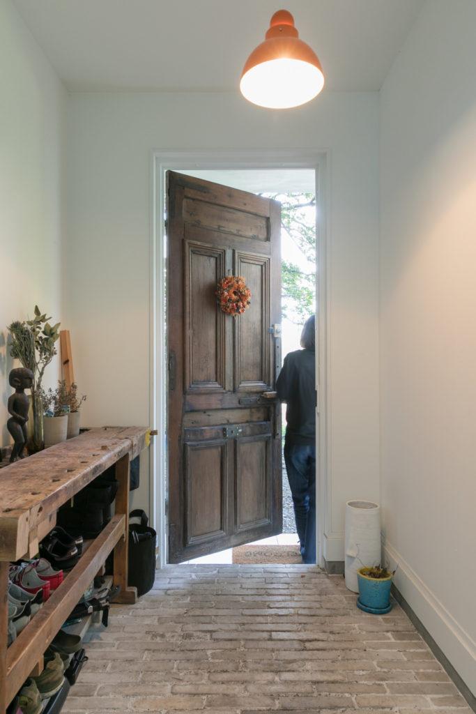 玄関ドアはフランス製のアンティーク。靴入れはアンティークの作業台にDIYで板を渡した。床は『toolbox』のチャイナブリック。