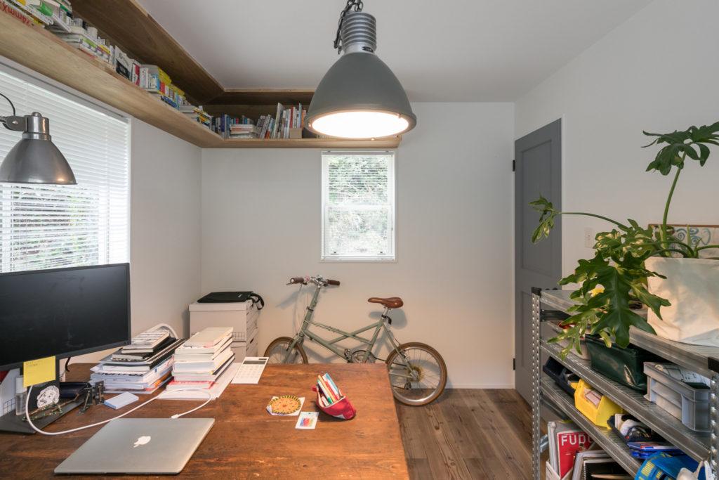 収納力たっぷりの天井近くの本棚、真似したいアイディアだ。「自転車が2階の部屋にあるのはなぜかというと、家の周りが急坂すぎて普通の自転車が使えなくなってしまったからです(笑)」