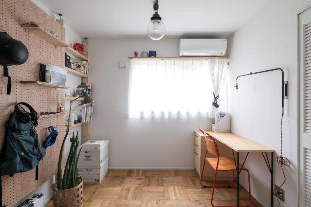 主にご主人が使っている2階のもうひとつの個室の床材は『toolbox』のスクールパーケットを使用。壁際の有孔ボードの収納棚はDIY。