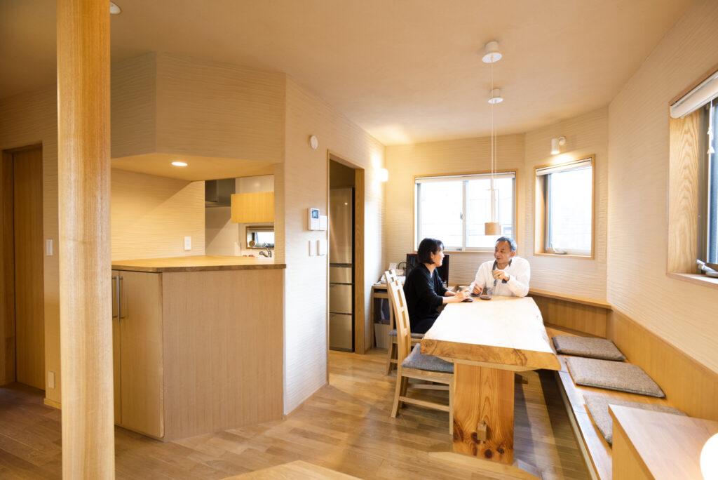 独立型のキッチン(左奥)には出入り口を2か所設け、回遊性をもたせた。たくさんの人が集えるようにと壁側にベンチを造作。座面下には客人が荷物を入れられるよう収納も付けた。