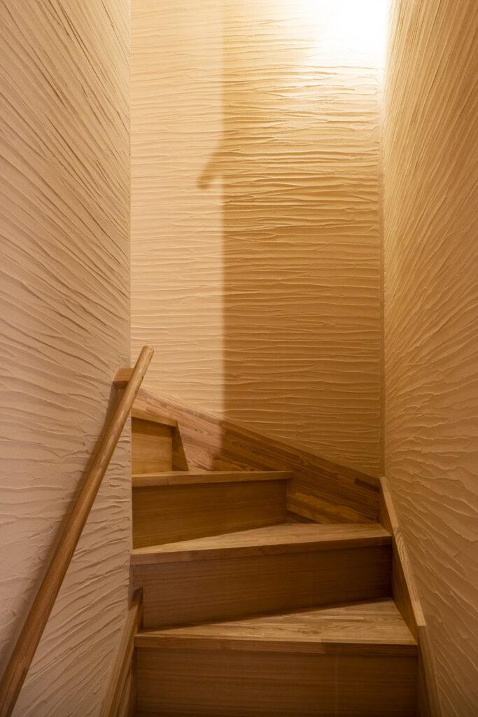 左官壁に囲まれた贅沢な階段室。全国の左官コンクールで入賞経験のある職人が仕上げた。その表情は圧巻。