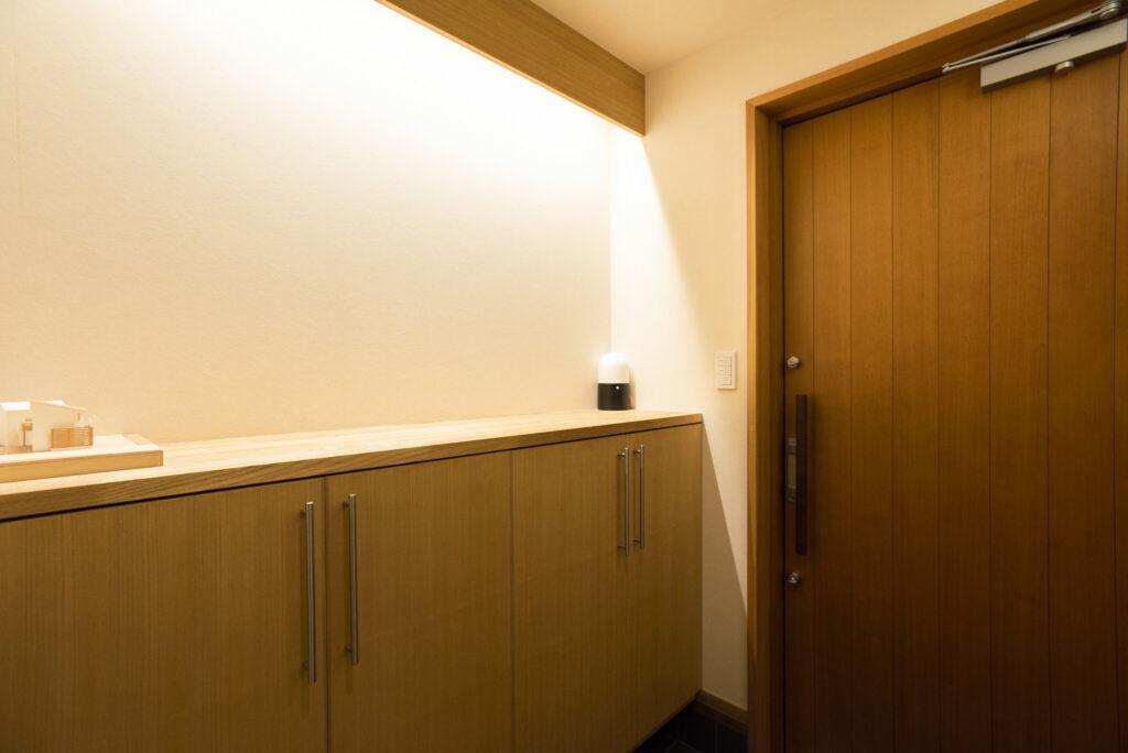 間接照明が美しい玄関。木製のドアにこだわった。