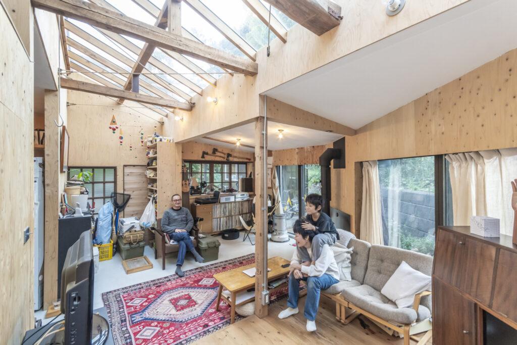 リビングを見る。天窓のあるところ以外の部分が元の天井の高さでかなり低め。壁には補強も兼ねて構造用合板が張られている。キッチンを土間にするリクエストはあったが、床の補強のためリビング部分も土間とした。