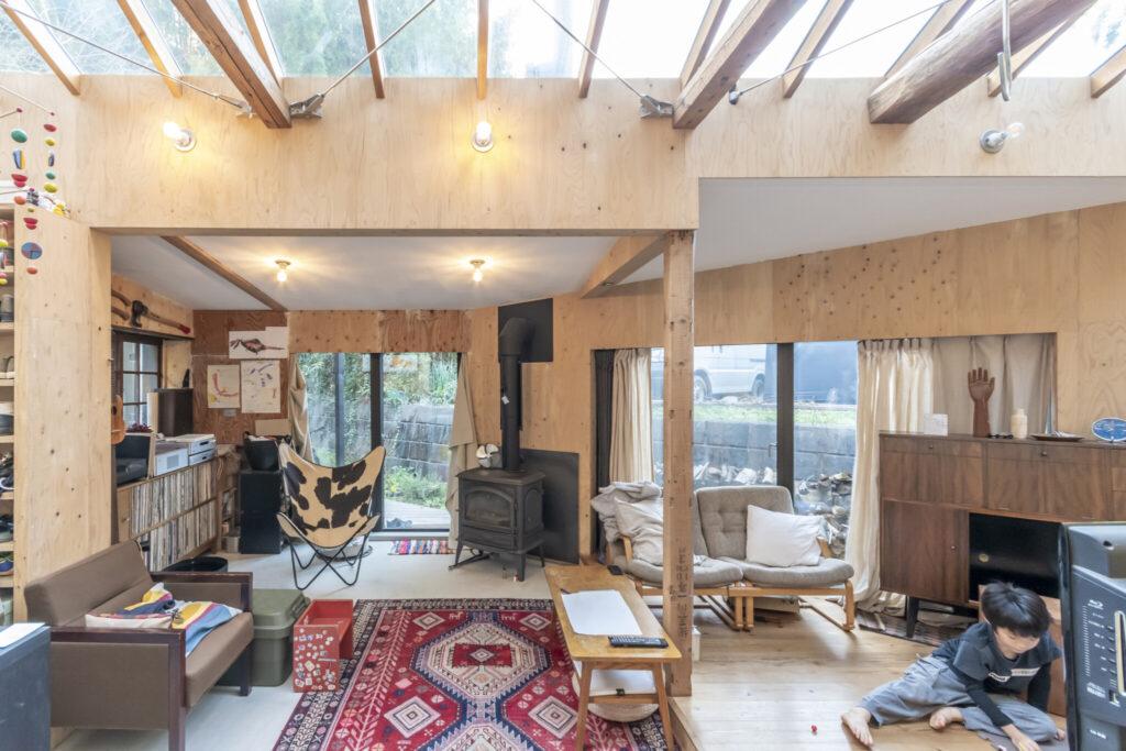 ストーブの左の開口が玄関。ワンルームのスペースの中に、形状や天井高・床の高さの違い、また明るさの違いにより居心地の異なる場所がつくられている。開口面が広く取られているためお2人の希望通り風通しのいい家になっている。