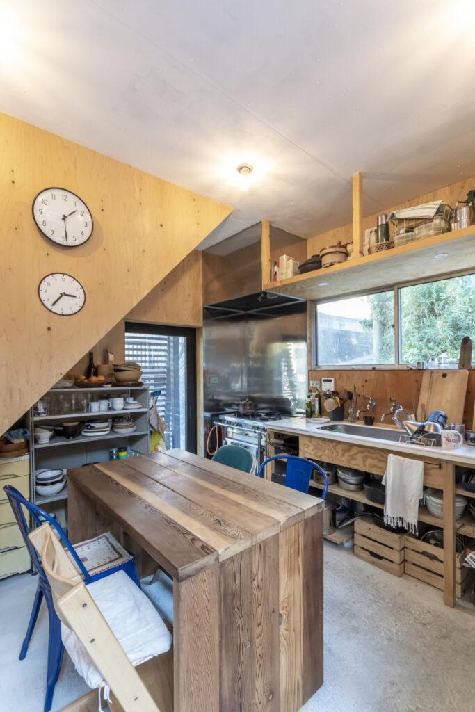 キッチン横の出入り口からはウッドデッキに出ることができる。時計のかかった壁の裏には階段がある。