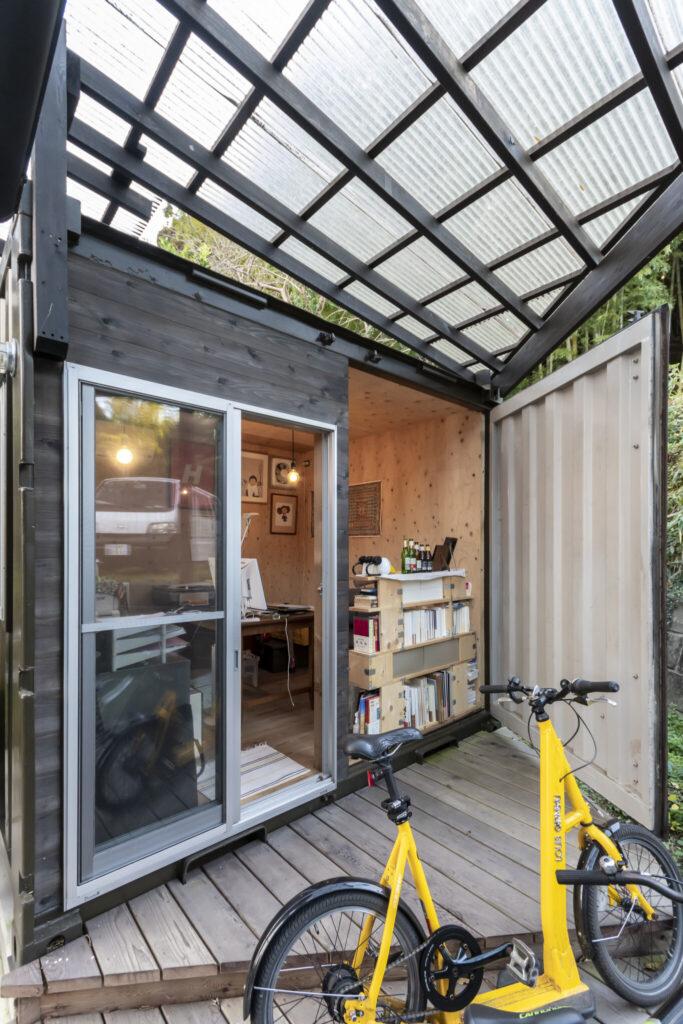 アトリエに改造したコンテナの扉を開けた状態。出入りは木製の壁に取り付けた開口から。
