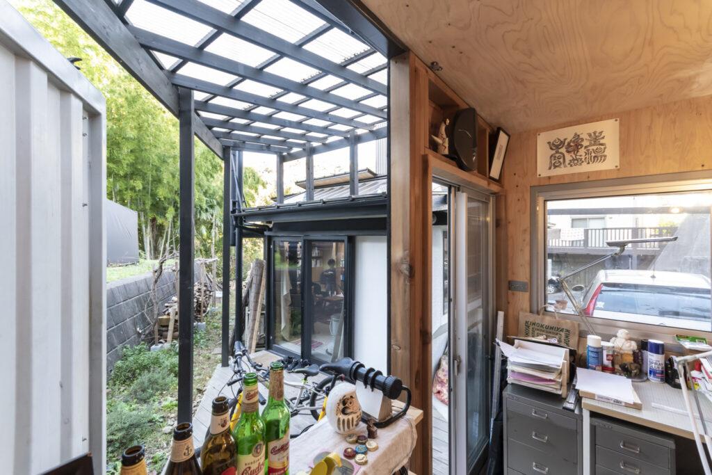 アトリエの内部には家と同じ構造用合板が張られている。コンテナの扉を開けるとその先にリビングが見える。コンテナは密閉度が高く息苦しくなるときがあるため、5~10月はこのように開けている。そうするととても快適に過ごせるという。
