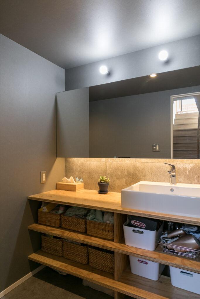 1階の洗面スペース。壁にはセメントの質感を活かした建築素材「SOLIDO」を使用し、シックな雰囲気に。
