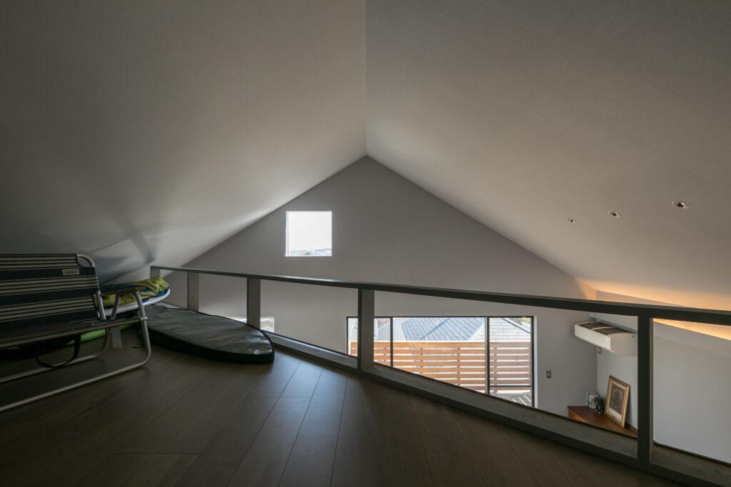 平面を対角線に分割した最上階のロフト。勾配天井によって低いところ、高いところが交わり、空間に奥行きを与えた。