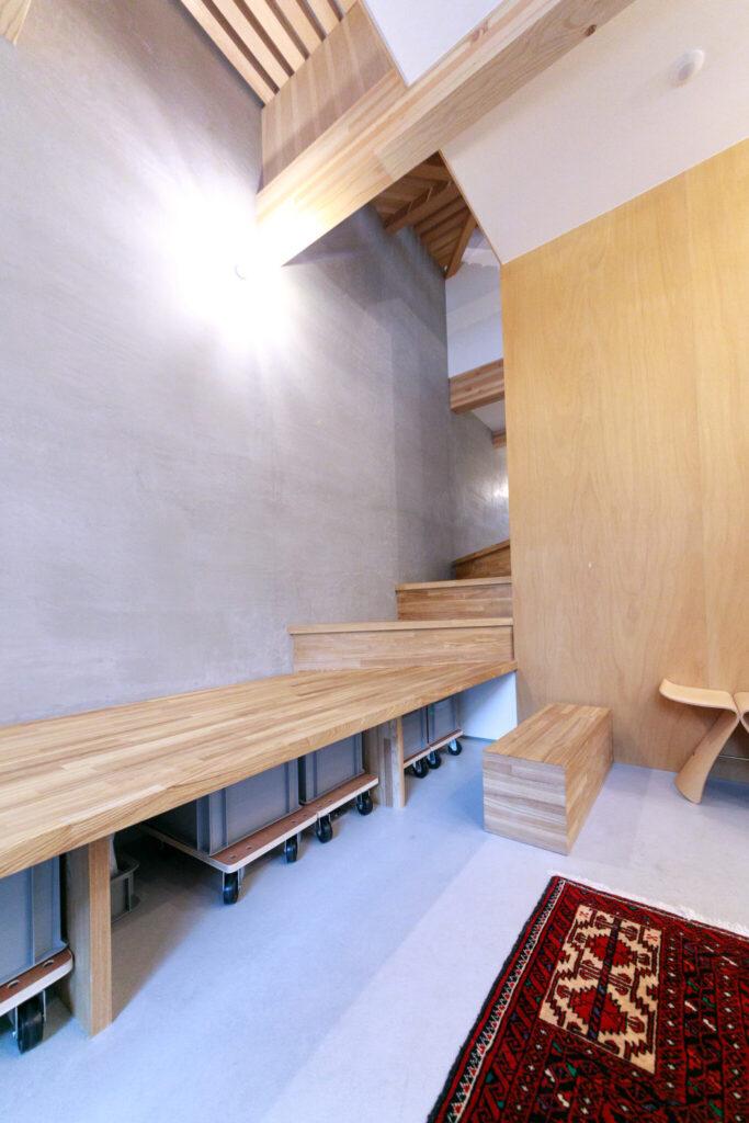 1階の玄関土間。階段の一部ともなるベンチを設置。ベンチ下には『アスクル』で注文した収納グッズを並べ、絵本などを収納