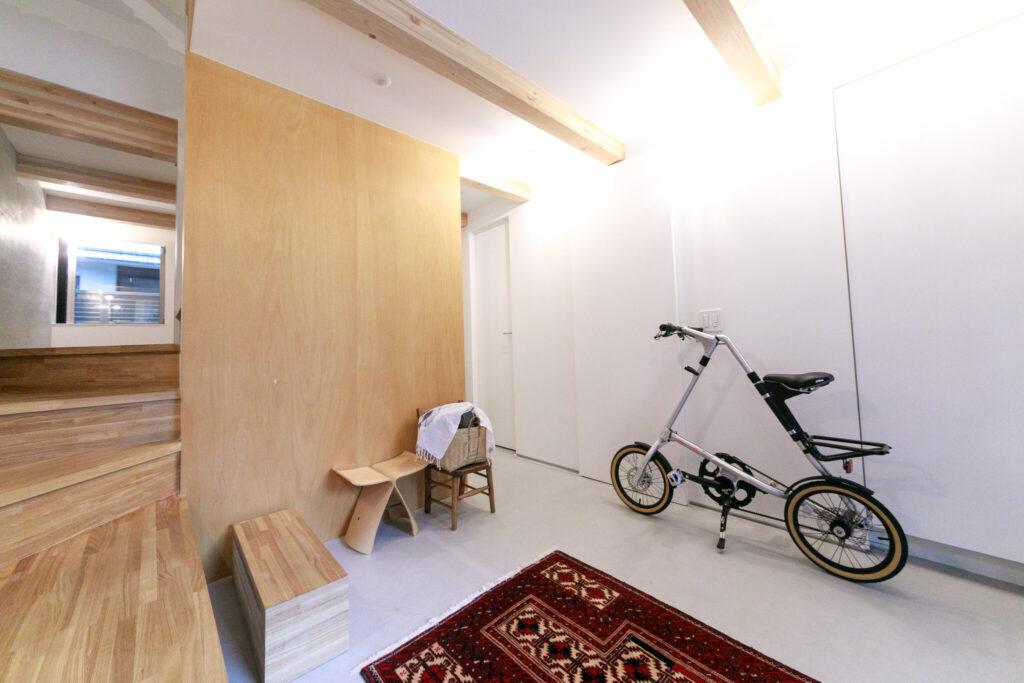 夫が愛用している折りたたみ自転車。自転車の奥がサニタリールーム。2階に続く階段下は収納になっている。その奥が寝室。