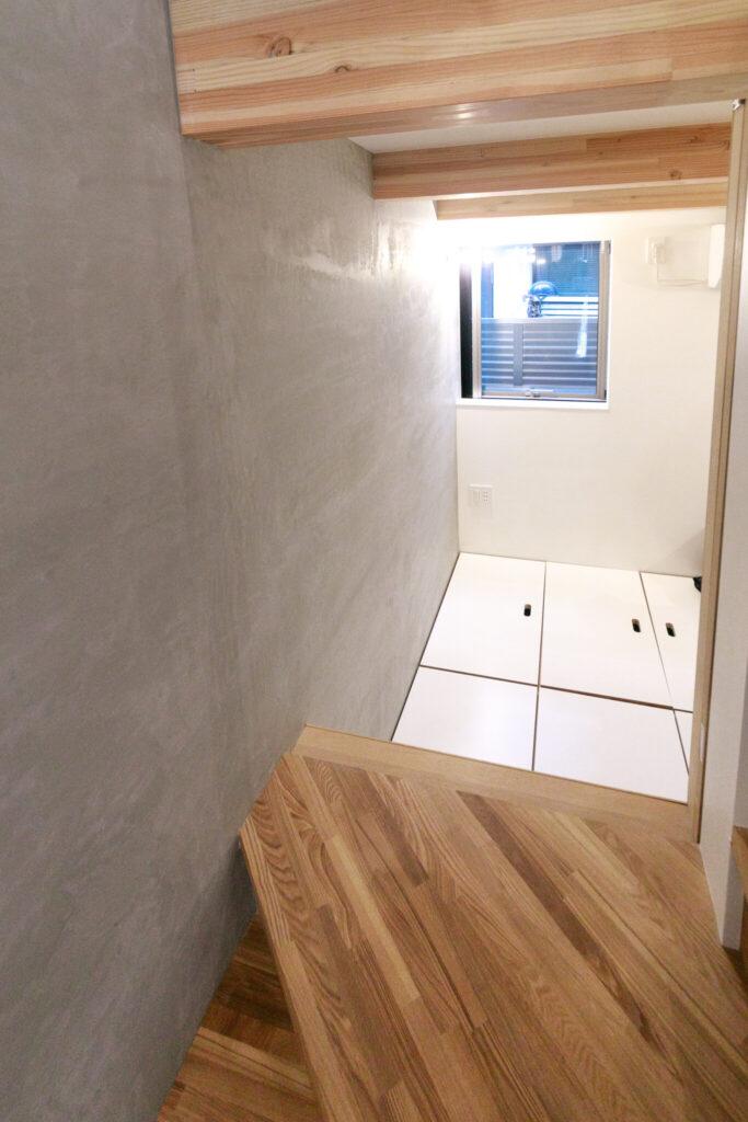 階段の途中にある小さな扉を開けると寝室につながる。通風にも一役。寝室には床下収納付きベッドを設え、収納力もアップ。