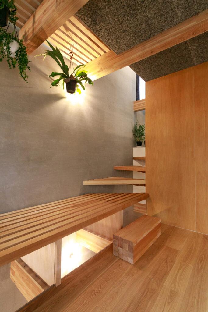 すのこ天井、すのこ状のベンチ&階段を通して、3階から1階へと光を落とす。3階から1階まで続くモルタルの壁により、空間につながりを持たせた。