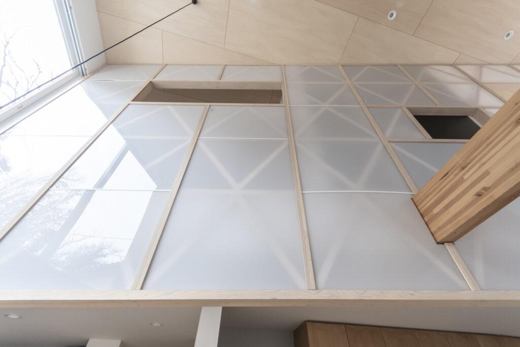 1階から見上げる。アクリルを通して木の格子が見える。半透明の壁のため遮断される感じがやわらげられている。左の開口がある部分が寝室で右が書斎。将来もう一部屋必要になった時は右の梁でスラブを受けて増床することも可能だ。