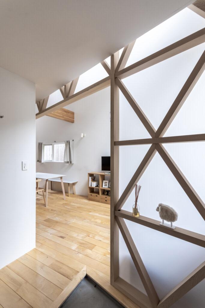 玄関からダイニングを見る。アクリルの壁を押さえている木の格子がデザイン的にも効いている。
