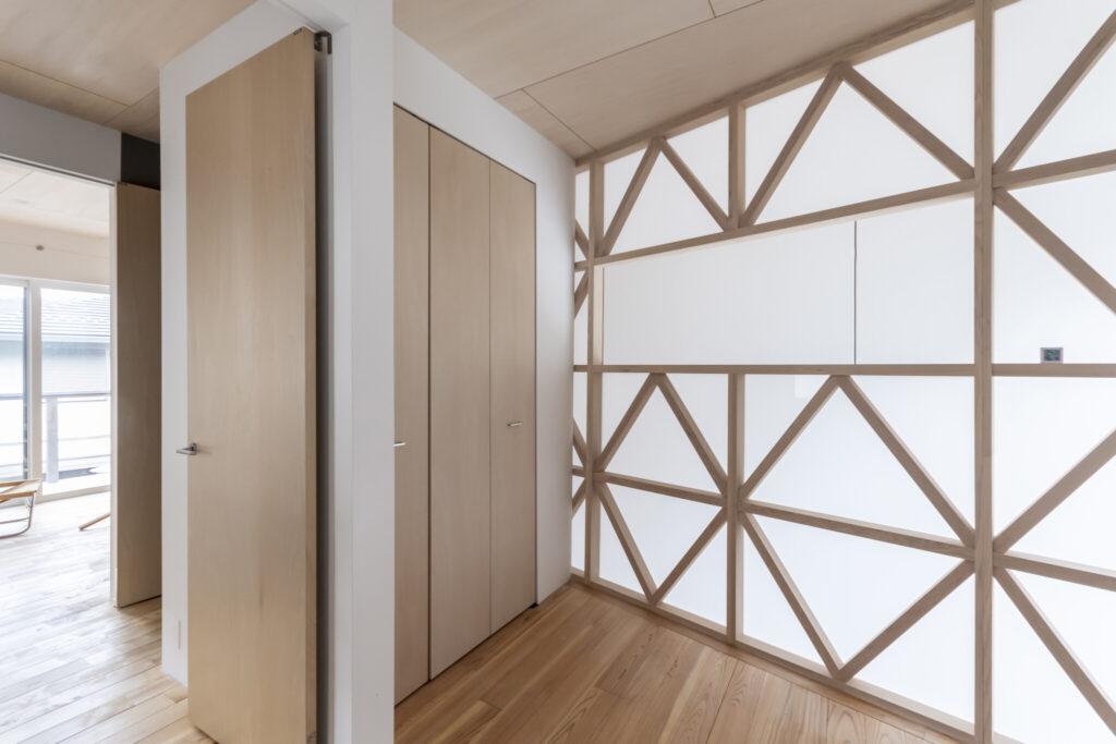 2階の寝室。木の格子のない部分は開口になっている。このスペースのみ床にスギ材が使われている。