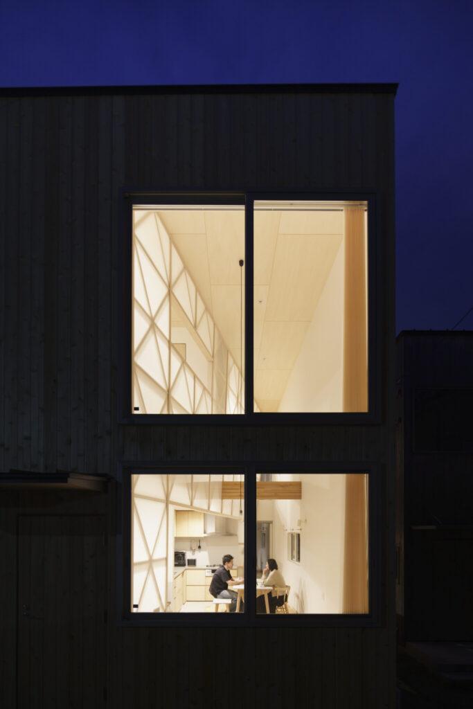 夜間に2階の明かりをつけると外部からはこのように見える。美術館のようだという人もいるという。(撮影:岡本 隆史、写真提供:etoa studio)。