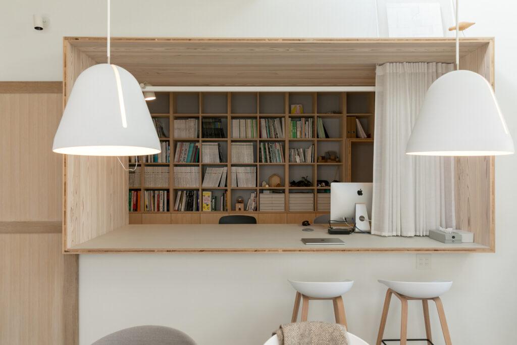 開口枠には奥行きがあり、デスクやカウンターとして両側から使える。カーテンを閉めれば独立した空間になる。