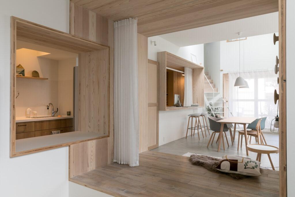ダイニングテーブルのある部屋と、手前のソファコーナーを分ける大きな開口枠。左手前の開口枠の向こうがキッチン。