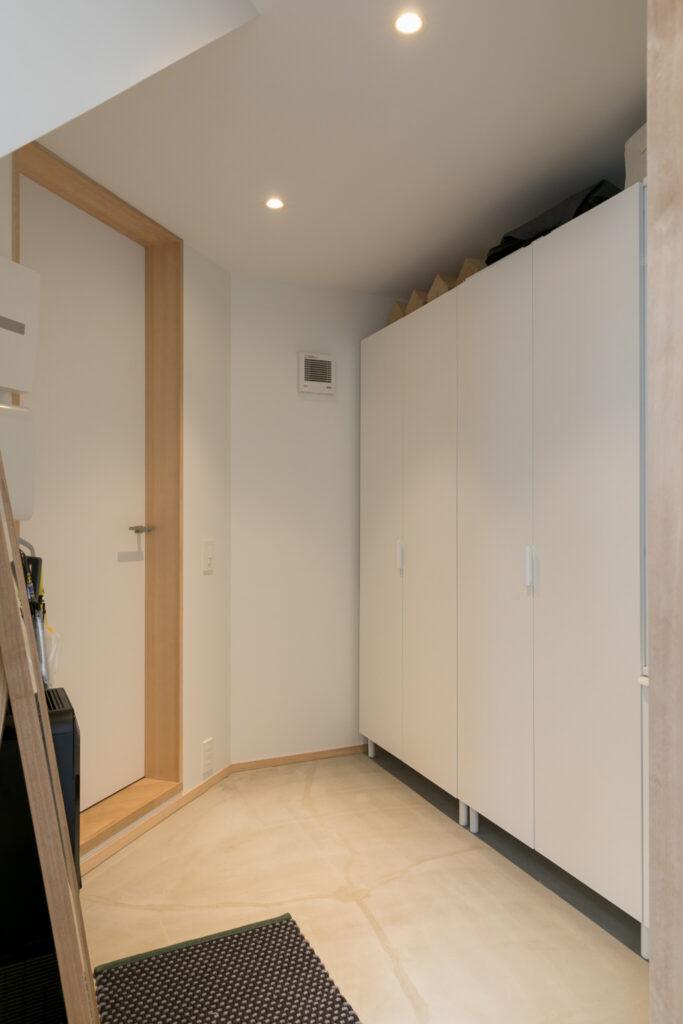 玄関横の扉を開けると、シューズクローゼットを備えた土間スペースになっている。奥の扉が書棚スペースにつながっていて、グルリと回遊できる。