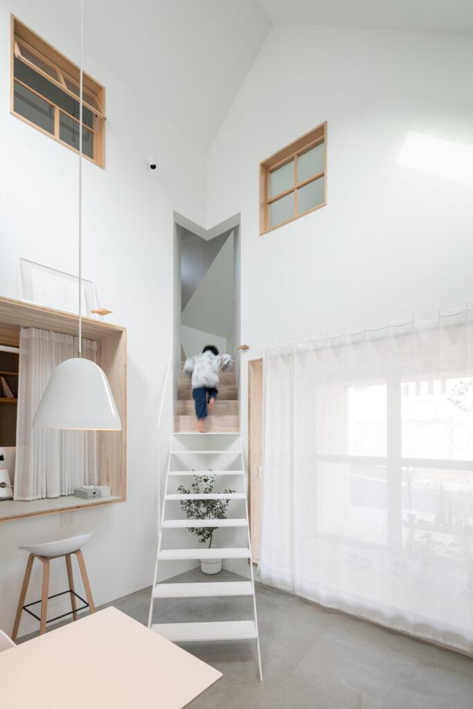 部屋の隅の異次元ポケットに吸い込まれていくようなダイニングにある階段は、白と木材を切り替えたデザイン。
