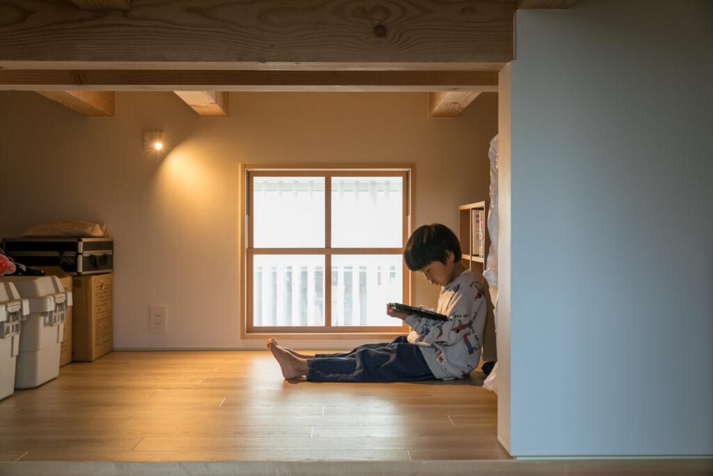 お籠り感を満喫できる場所も家のあちこちに。奏人くんが本を読んでいるのは、中二階の収納庫。