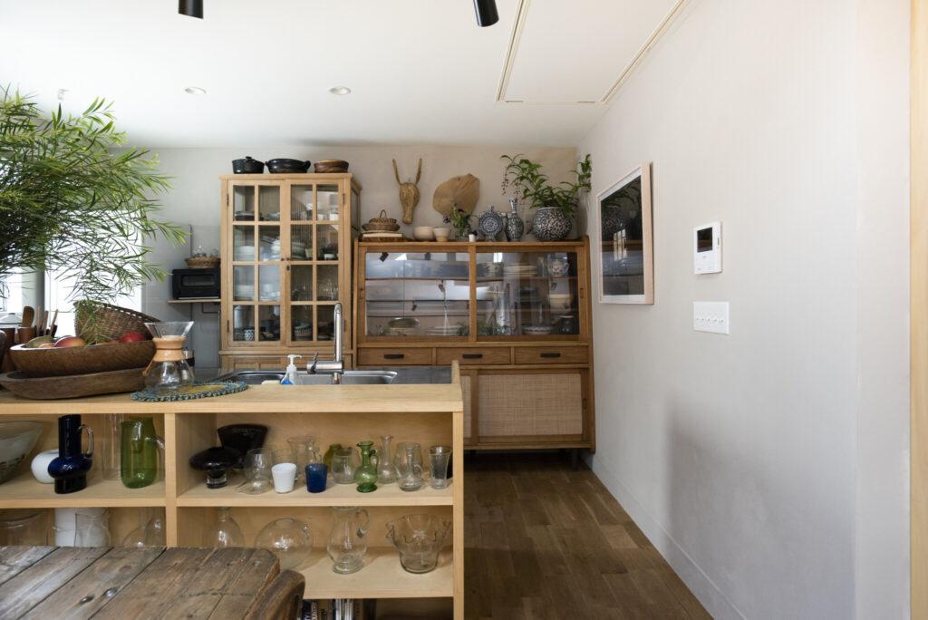 対面式キッチンを希望した安樹子さん。もとは壁付けタイプのキッチンに、造作で飾り棚をつけコストダウン。カウンター上のグリーンから奥の食器棚上のグリーンへと視線が行く飾り方にも注目。