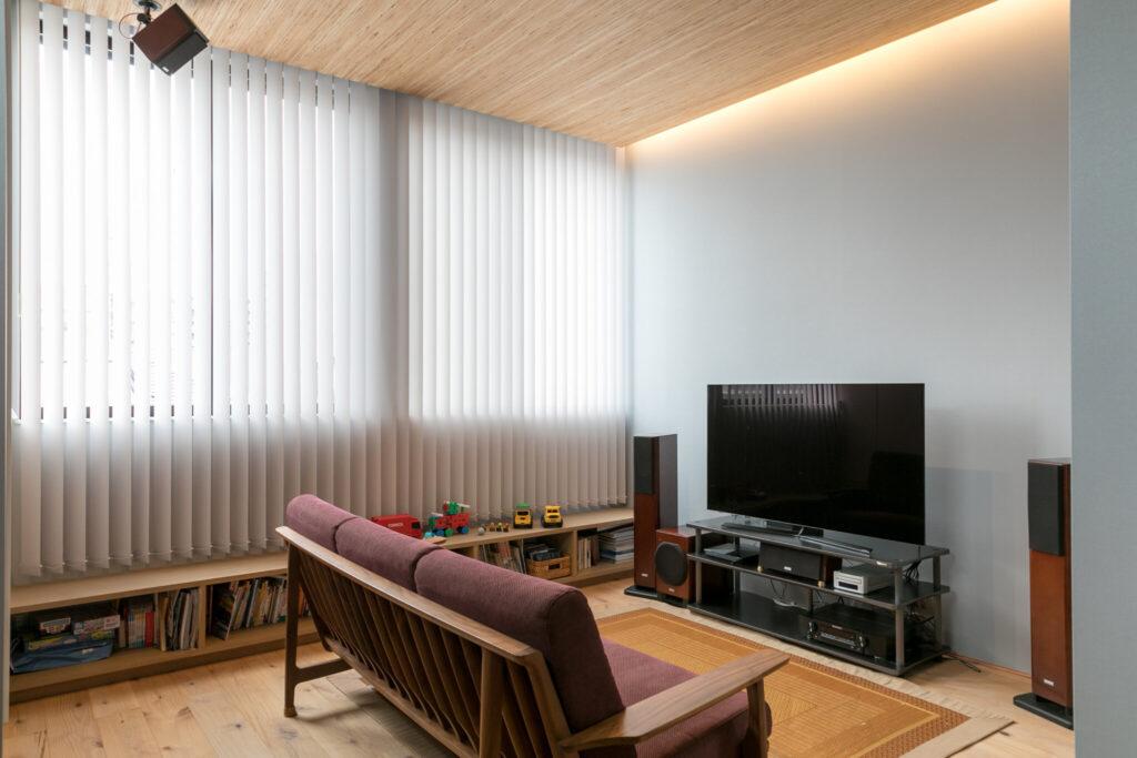 ご主人が特に気に入っているというリビング。青い壁紙とマッチするワインレッドのソファは井上さんセレクト。天井部にはスピーカーを配し、迫力のある音響で映画鑑賞を楽しんでいるという。
