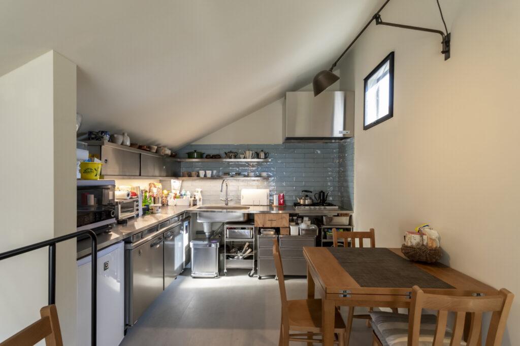 奥さんの希望はアイランド型のキッチンだったが、面積の関係からL字になった。冷蔵庫も同じ理由で業務用のものを選択。ステンレス製のキッチンは奥さんの希望で、壁は冷たい印象にならないように水色のタイルにした。