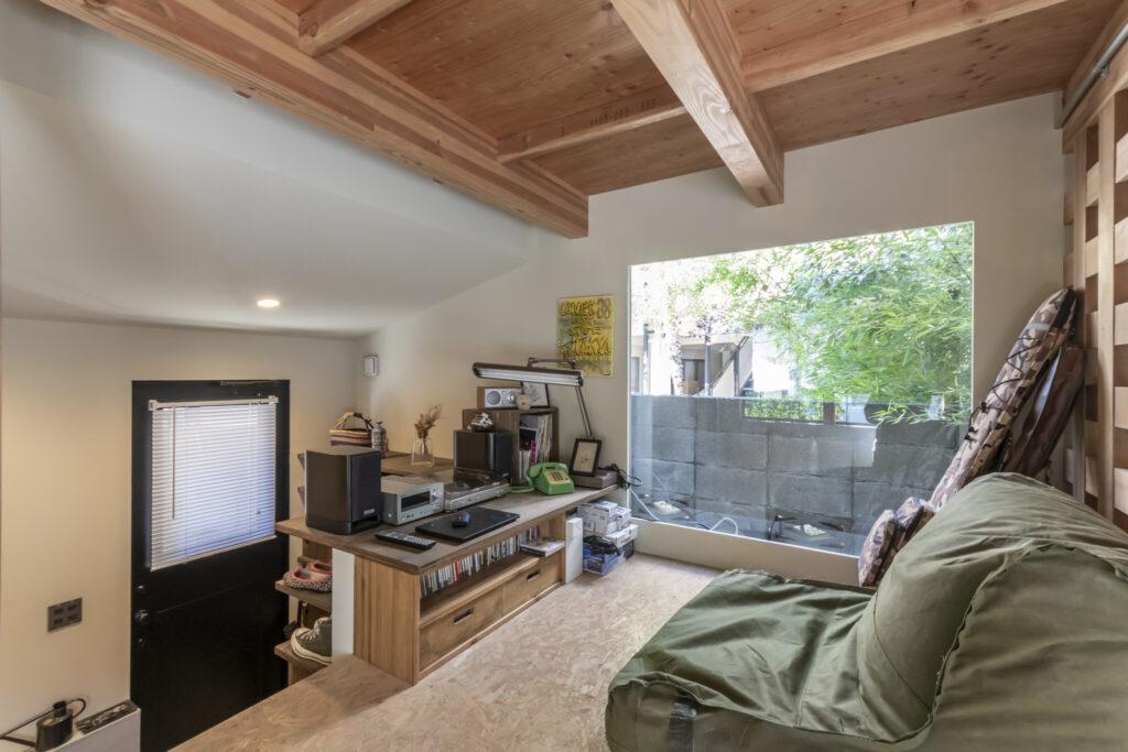 玄関を入ってすぐ目の前に見えるのがロフトと呼ばれているスペース。仕切られていないが、関根さんは「自分の個室みたいなイメージでとても気に入っている」という。大きな開口から見える隣地の緑が目に心地よい。