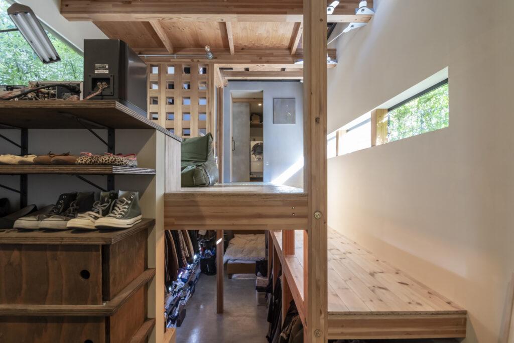 玄関付近から見る。住宅には珍しいずれた断面構成が面白い。左側の部分には靴が置かれているがショップのディスプレイ棚のような印象を受ける。