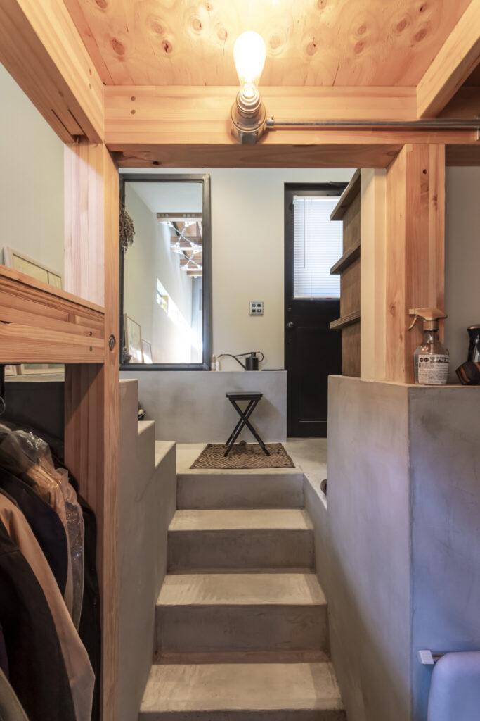 スチール製の黒い玄関ドアの隣には黒い縁の姿見が置かれている。