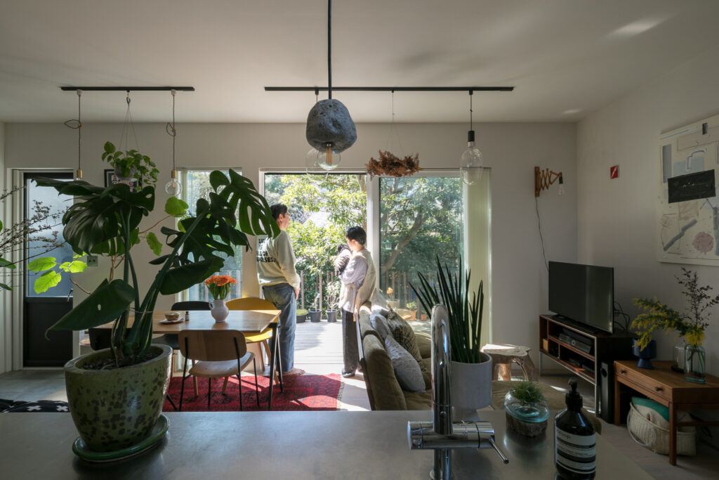 窓の外に緑の借景が広がる。室内にもたっぷりのグリーン。広いウッドデッキではバーベキューも。