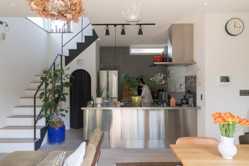 キッチンは抑えたデザインが美しいオールステンレスのもの。黒いカーテンをかけたアーチ状の入口の奥はパントリー。