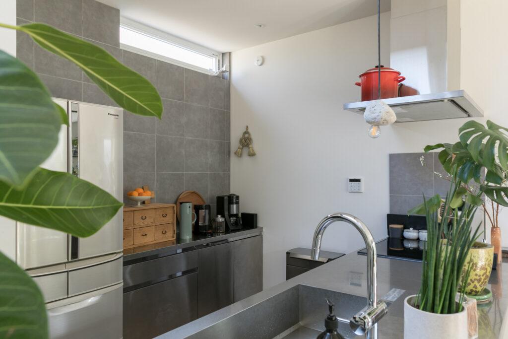 キッチン背面の棚もステンレス。グレーのタイルのモノトーンの組み合わせの中に、温かさを感じさせるアンティークの小物入れ。