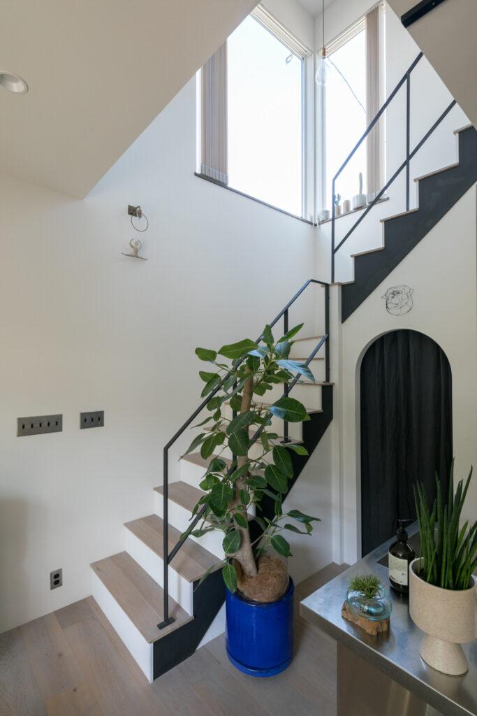 階段の吹き抜けの高窓から明るい光が差し込む。階段下のスペースを生かしたパントリーには黒のカーテンを下げた。