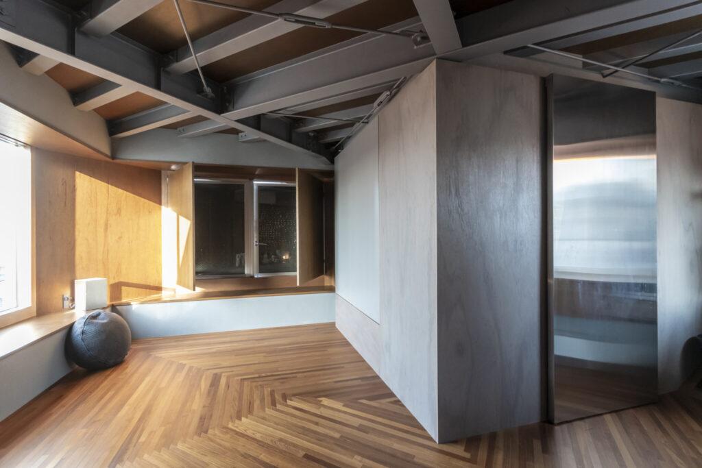"""4階の北側の出窓(奥)は、光や熱は遮断し、風のみを取り入れる""""開く壁""""となっている。"""