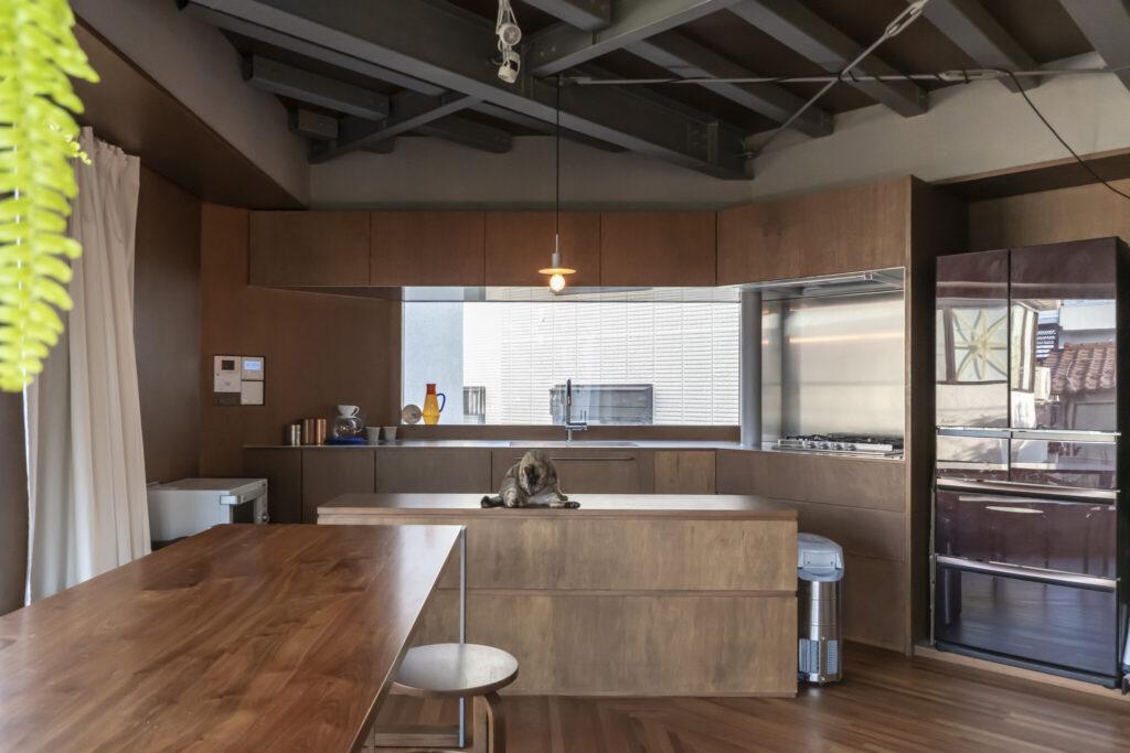 2階の南東側の出窓にはキッチンを設えた。シンプルな『グローエ』のキッチン水栓を採用したすっきりとした造りに。手前のダイニングテーブルは藤さん夫妻のオリジナルデザインで、奥の作業台と高さを合わせた。付ければL字型のテーブルとしても使用可能。