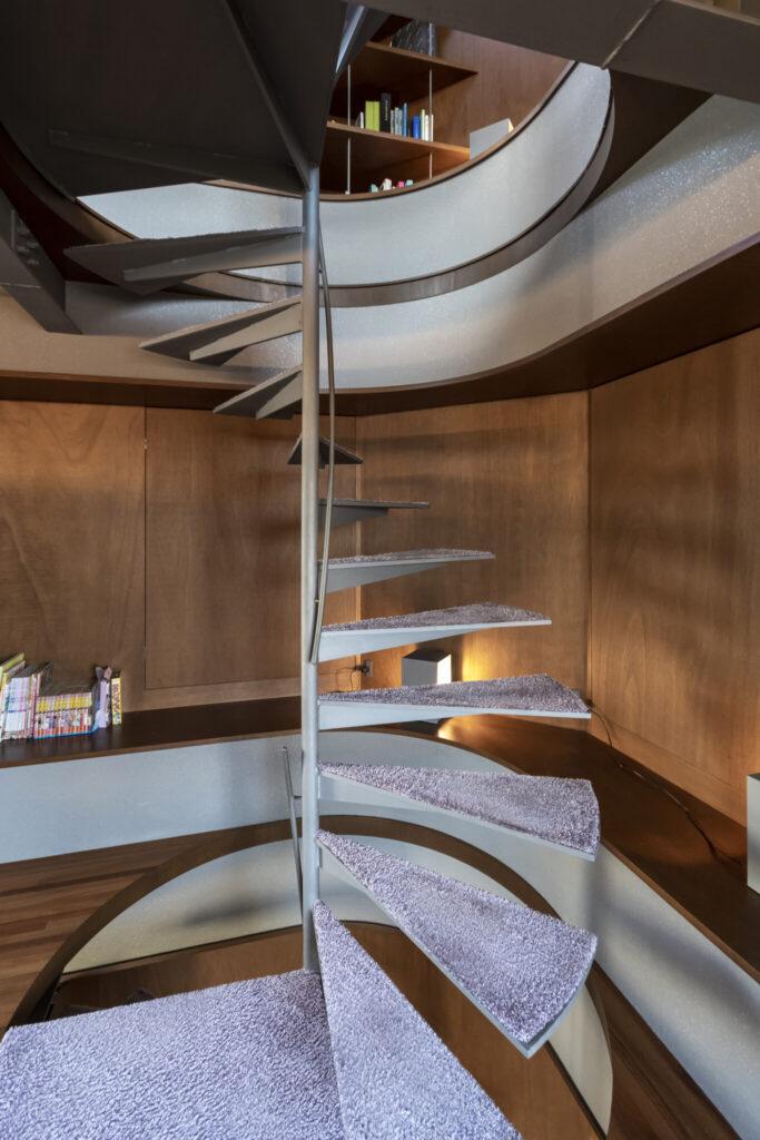華奢な螺旋階段は内側に手すりを付け、より開放的に。左官壁と鉄部は雲母が入った塗装でキラキラと輝き、奥行きを感じさせる。