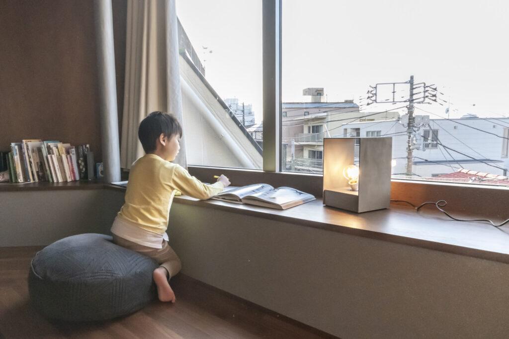 持ち運びができるオリジナルの照明器具を置いて、4階の出窓でお絵描きをする息子さん。