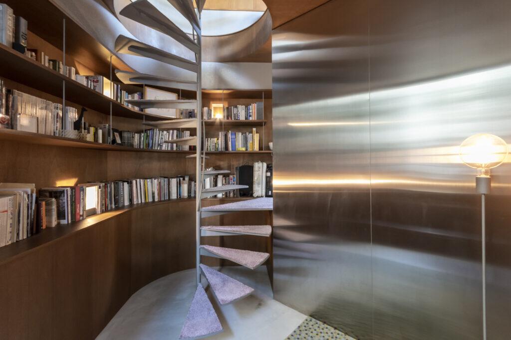 地階から屋上までつながる螺旋階段。上部からの光を取り込んでいる。ステンレスの壁が光を反射し、広くみせる効果も。書棚は、本の上や前にあえてスペースを造り、猫たちが歩けるようにした。