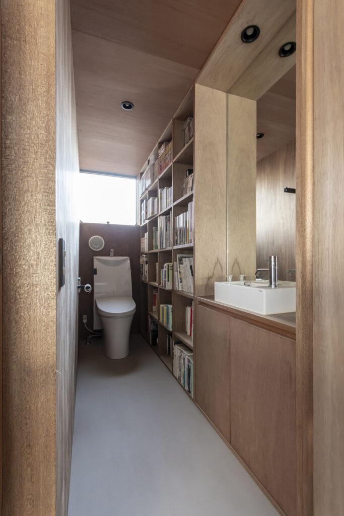 中2階の真ん中につくられた手洗い・トイレスペース。壁に本棚がつくられている。