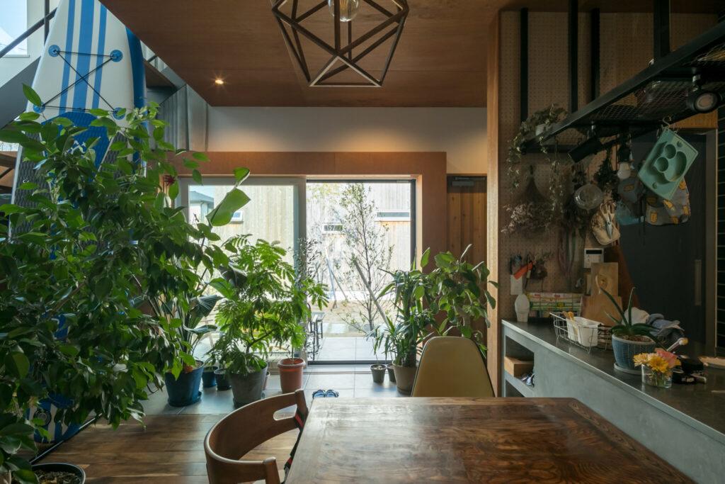 窓辺はテラスまでひとつながりの土間風のタイル敷に。室内はたっぷりの緑。