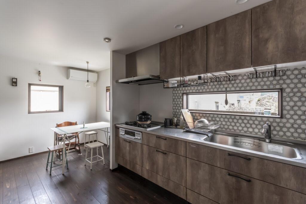 他の部屋とは趣が異なる、クールな印象のキッチン。壁面タイルは、シンク側とカウンター側で同じデザインの色違いにした。